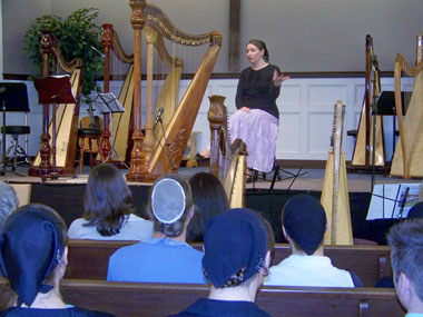 Joanna speaking to a group of harpists